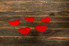 De dagachtergrond van valentijnskaarten met harten Donkere houten bedelaars Stock Foto