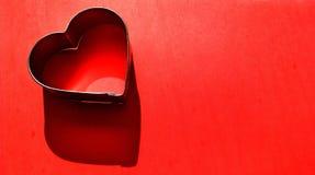 De Dagachtergrond van Valentine met het gelezen hart van de koekjessnijder Royalty-vrije Stock Foto's