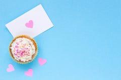 De dagachtergrond van Valentine ` s De dagkaart van Valentine ` s en cupcake met exemplaarruimte op de blauwe achtergrond Stock Foto