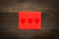De dagachtergrond van Valentine ` s De Dagkaart van Valentine ` s met rode harten op het houten bureau Stock Afbeelding