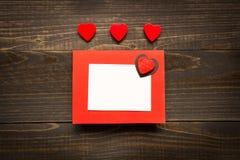 De dagachtergrond van Valentine ` s De Dagkaart van Valentine ` s met rode harten op het houten bureau Stock Foto's