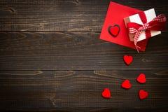 De dagachtergrond van Valentine ` s Giftvakje, rode harten en de dagkaart van Valentine ` s met exemplaarruimte op het houten bur Royalty-vrije Stock Fotografie