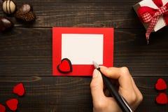 De Dagbureau van Valentine ` s Vrouwelijke hand met pen en de Dagkaart van Valentine ` s op de houten achtergrond Stock Foto's