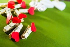 De dagconcept van de valentijnskaart ` s De rode wasknijpers van de hartvorm en witte houten harten op groene achtergrond Stock Fotografie