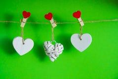De dagconcept van de valentijnskaart ` s Witte houten harten vast met wasknijpers op koord op groene achtergrond Stock Fotografie