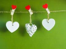 De dagconcept van de valentijnskaart ` s Witte houten harten vast met wasknijpers op koord op groene achtergrond Royalty-vrije Stock Afbeeldingen