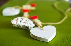 De dagconcept van de valentijnskaart ` s Witte houten harten vast met wasknijpers op koord op groene achtergrond Royalty-vrije Stock Afbeelding