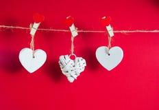 De dagconcept van de valentijnskaart ` s Witte houten harten vast met wasknijpers op koord op rode achtergrond Royalty-vrije Stock Afbeelding