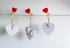 De dagconcept van de valentijnskaart ` s Witte houten harten vast met wasknijpers op koord op witte achtergrond Royalty-vrije Stock Afbeeldingen