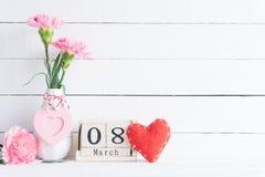 De dagconcept van internationale vrouwen Roze anjerbloem in vaas en rood hart met 8 Maart tekst op houten scheurkalender op wit royalty-vrije stock fotografie