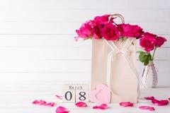 De dagconcept van internationale vrouwen Roze rozen in document zak met 8 Maart tekst op houten scheurkalender op witte houten ac royalty-vrije stock foto