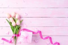 De dagconcept van internationale vrouwen Roze tulpen en rood hart met giftdoos op witte en roze houten achtergrond royalty-vrije stock foto's