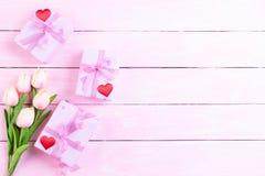 De dagconcept van internationale vrouwen Roze tulpen en rood hart met giftdoos op witte en roze houten achtergrond stock fotografie