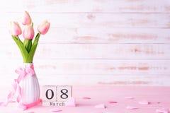 De dagconcept van internationale vrouwen Roze tulpen en rood hart met 8 Maart tekst op houten scheurkalender op witte houten acht stock fotografie