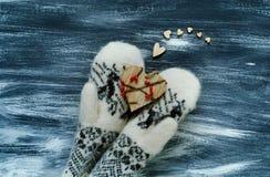 De dagconcept van Valentine ` s, houten hart op vuisthandschoenen met Skandinavisch ornament op blauwe achtergrond, natuurlijk li Stock Foto