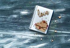 De dagconcept van Valentine ` s, houten inschrijving op liefde en harten op een notitieboekje met een kalender, natuurlijk licht, Royalty-vrije Stock Afbeeldingen