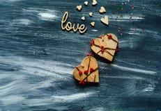 De dagconcept van Valentine ` s, houten liefdeinschrijving en harten op blauwe achtergrond, natuurlijk licht, ruimte voor tekst Royalty-vrije Stock Foto's