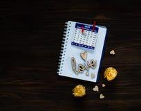 De dagconcept van Valentine ` s, houten liefdeinschrijving en harten op een notitieboekje met kalender, natuurlijk licht, ruimte  Stock Afbeeldingen