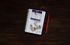 De dagconcept van Valentine ` s, houten liefdeinschrijving en harten op een notitieboekje met kalender, natuurlijk licht, ruimte  Royalty-vrije Stock Afbeelding