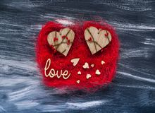 De dagconcept van Valentine ` s, houten liefdeinschrijving en harten op een rode textuur op een donkere achtergrond, natuurlijk l Royalty-vrije Stock Afbeeldingen