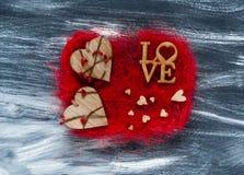 De dagconcept van Valentine ` s, houten liefdeinschrijving en harten op een rode textuur op een donkere achtergrond, natuurlijk l Stock Afbeelding