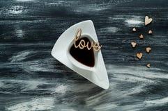 De dagconcept van Valentine ` s, witte kop met koffie op kleine hartenachtergrond en liefdewoorden op blauwe houten textuur, natu Stock Afbeeldingen