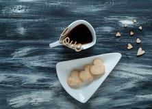 De dagconcept van Valentine ` s, witte kop met koffiekoekjes in de vorm van harten op blauwe houten textuur, hoogste mening Royalty-vrije Stock Foto's