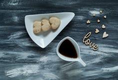 De dagconcept van Valentine ` s, witte kop met koffiekoekjes in de vorm van harten op kleine hartenachtergrond op blauwe houten t Royalty-vrije Stock Fotografie