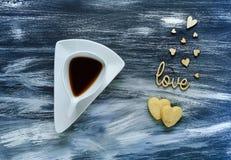 De dagconcept van Valentine ` s, witte kop met koffiekoekjes in de vorm van harten op kleine hartenachtergrond op blauwe textuur, Royalty-vrije Stock Afbeeldingen