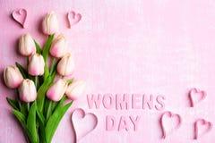 De dagconcept van vrouwen Roze tulpen en document harten met Houten brieven die de dag vormen die van woordvrouwen op roze en wit stock fotografie