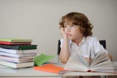 De dagdromenschooljongen zit bij een schoolbank Stock Fotografie