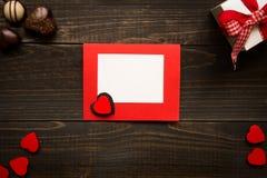 De Dagkaart van Valentine ` s op de houten achtergrond Giftdoos, rode harten en chocolade op het houten bureau Royalty-vrije Stock Foto's