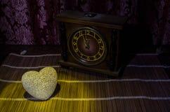 De Dagsamenstelling van Valentine met snoepje die multicolored hart op donkere achtergrond en oud uitstekend klok, tijd en liefde Stock Foto's