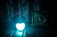 De Dagsamenstelling van Valentine met snoepje die multicolored hart op donkere achtergrond en oud uitstekend klok, tijd en liefde Stock Afbeeldingen