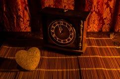De Dagsamenstelling van Valentine met snoepje die multicolored hart op donkere achtergrond en oud uitstekend klok, tijd en liefde Royalty-vrije Stock Afbeeldingen