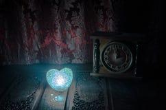 De Dagsamenstelling van Valentine met snoepje die multicolored hart op donkere achtergrond en oud uitstekend klok, tijd en liefde Stock Foto