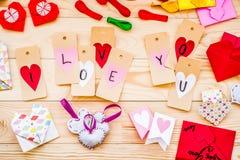 De Dagvakantie van Valentine ` s mooie hand - gemaakte decoratie: document harten, klemmen, origamienveloppen op houten achtergro Stock Fotografie
