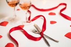 De dagvertoning van Valentine van een dinervoorbereiding met bestek, rood lint, glazen wijn en hartsymbolen royalty-vrije stock foto's
