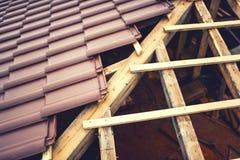 De dakbouw met ceramische bruine tegels op houten, houtstructuur Geometrische distributie van daktegels bij huisbouw Stock Fotografie