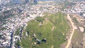 De daken van de de meningstempel van het vogeloog op groene heuvel tegen stad stock footage