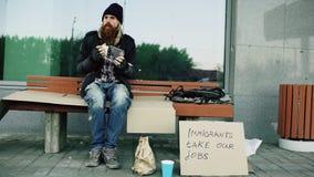 De dakloze en werkloze Europese mens met kartonteken eet sandwich op bank bij stadsstraat wegens immigrantencrisis Royalty-vrije Stock Foto's