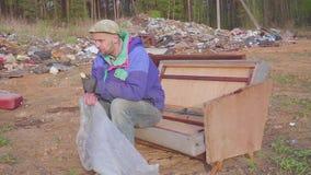 De dakloze mens eet bij de stortplaats sociale video stock footage