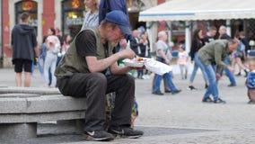 De dakloze mens met baard eet van plastic plaatzitting op de straat stock videobeelden