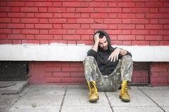 De dakloze de mensendrug en alcohol wijden zitting alleen en gedeprimeerd op de straat royalty-vrije stock foto