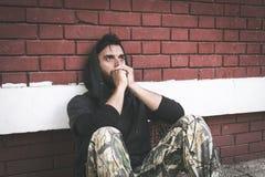 De dakloze de mensendrug en alcohol wijden zitting alleen en gedeprimeerd op de straat stock foto's