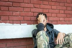 De dakloze de mensendrug en alcohol wijden zitting alleen en gedeprimeerd op de straat royalty-vrije stock afbeelding