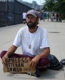 De dakloze veteraan pauzeert aangezien hij voor geld bedelt Stock Afbeeldingen