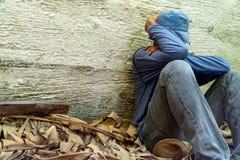 De daklozen droegen een grijze hoed en een grijs lang-kokeroverhemd Slaapt wegens uitputting, met het achter leunen tegen Siemens stock foto