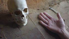 De dalende hand van een dode verslaafde met een spuit tegen de achtergrond van de schedel langzame motie stock video