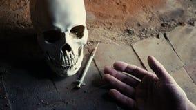 De dalende hand van een dode verslaafde met een spuit tegen de achtergrond van de schedel langzame motie stock footage